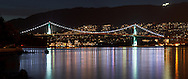 The lights of the Lions Gate Bridge and West Vancouver reflect in Burrard Inlet at Stanley Park - Vancouver, British Columbia, Canada