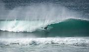 A surfer catches a wave at Salmon Creek Beach, Sonoma Coast State Park, California