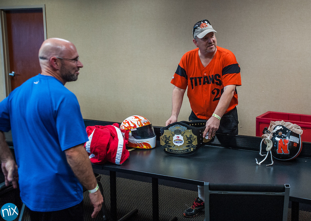 Darin Roberts, left, principal of Furr Elementary School, and Tim Farrar, from Northwest Cabarrus Middle, check out the new champions belt prior to the Principal School Bus Slobberknocker at Charlotte Motor Speedway Tuesday night during the Summer Shootout.