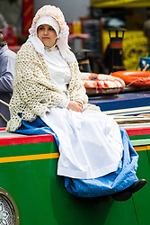 Little Venice, London, April 30th 2017. Narrowboaters from all over the uK gather for the annual Canalway Cavalcade, held on the May Day Bank holiday weekend, organised by the Inland Waterways Association, where boaters get the chance to display their immaculately prepared and brightly painted craft as well as compete in various manoeuvring tests. PICTURED: A girl in traditional dress sits on the roof of her narrowboat as it glides along the canal.<br /> Credit: ©Paul Davey<br /> To licence contact: <br /> Mobile: +44 (0) 7966 016 296<br /> Email: paul@pauldaveycreative.co.uk<br /> Twitter: @pauldaveycreate