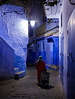 CHEFCHAOUEN, MOROCCO - CIRCA APRIL 2017: Moroccan woman walking in the streets of Chefchaouen at night.