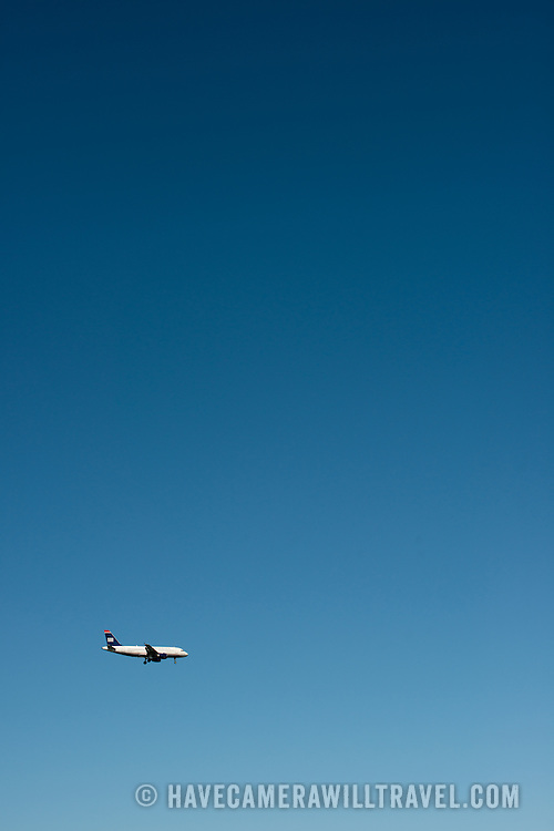 A US Airways jet comes in to land with its landing gear down, flying against a beautiful clear blue sky.