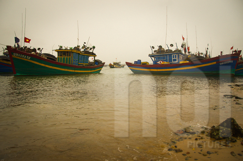 Colorful fishermen boats are anchored to the shore. Dong Hoi, Quang Binh, Viet Nam. Asia. Vietnamese flags float on each boat.