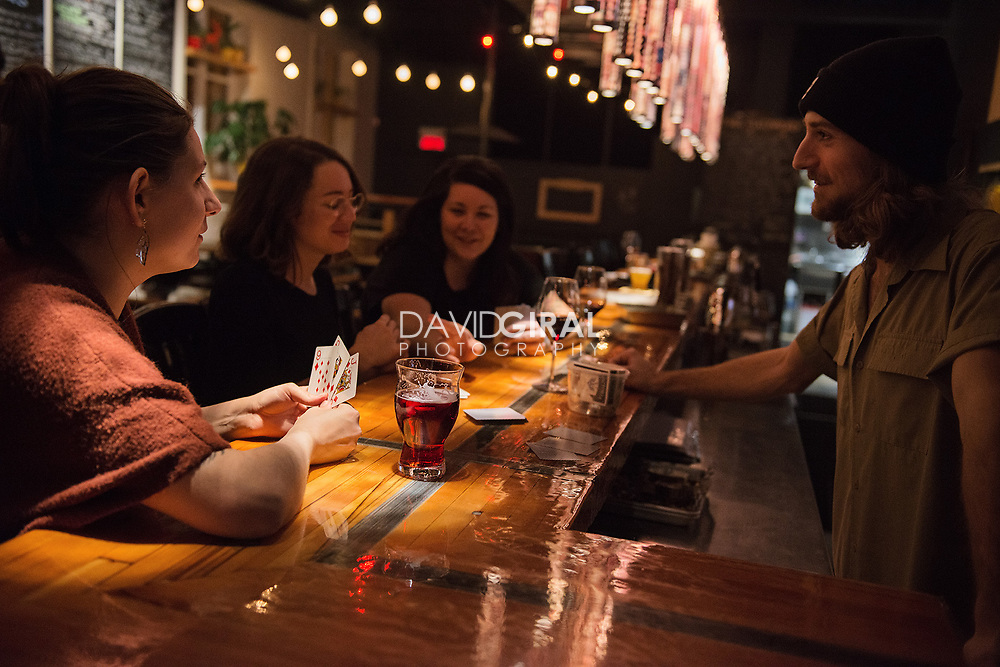 Patrons at the bar enjoying a card game with the barman - Yïsst Bar, 901, rue St.-Zotique Est, Montreal