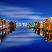 I have taken this photo in a very fcalm winter nights with absolutely gorgeous lights around. Trondheim with picturesque, tiny, wooden houses. This idyllic neighbourhood on the east side of the Nidelva river features old timber buildings, originally the homes of the working class. Now restored, Bakklandet is a charming mixture of houses, shops and cafés.<br />