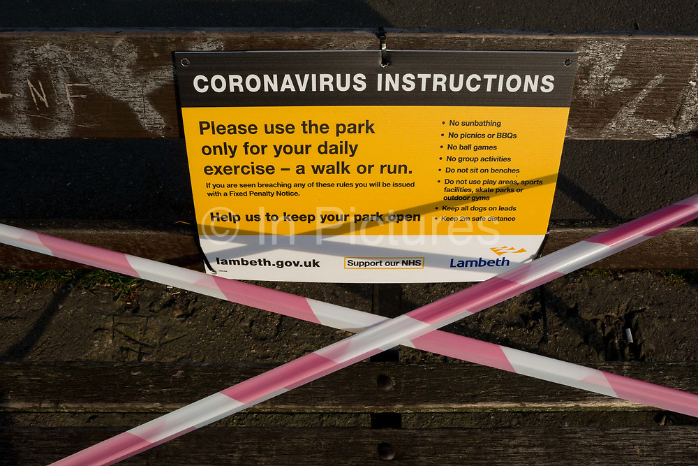 At the beginning of the Easter Bank Holiday weekend, Lambeth council have attached to park benches, notices aimed at the public about restrictions that the UK governments have imposed during the Coronavirus pandemic lockdown, now at the end of its second week, in Ruskin Park, a south London green space, on 9th April, in London, England.