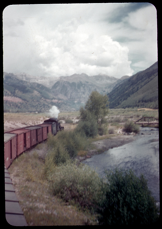 RGS eastbound freight train approaching Telluride along San Miguel River as seen from the caboose.<br /> RGS  Keystone, CO  Taken by Rasmussen, Forest - maybe 7/17/1951<br /> Thanks to Don Bergman for additional information.