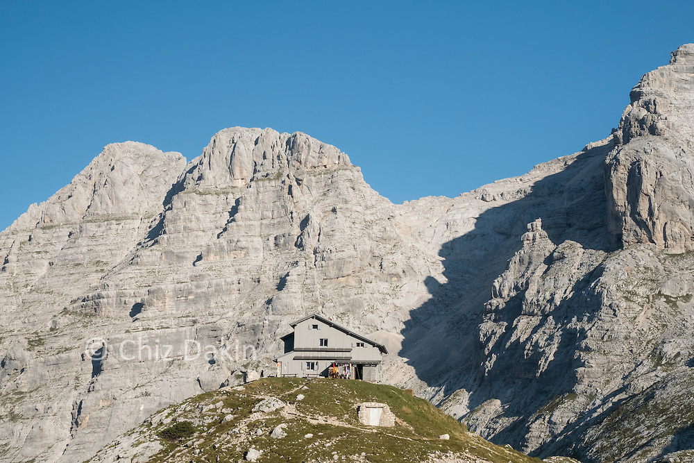 The Pogačnikov Dom mountain hut appears perched on it's own grassy mound