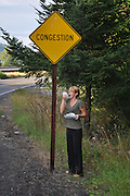 Humorous photograph of a woman sneezing into a Kleenex while standing under a CONGESTION warning sign.