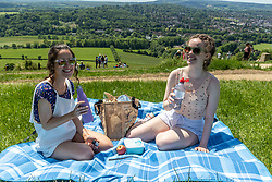 Licensed to London News Pictures. 05/06/2021. Dorking, UK. After the heavy rains yesterday, sisters (left) Amy 23 and Claire Whitehead 19 from Ealing enjoy the warm sunshine with a picnic on Box Hill in Surrey as the fine June weather continues. The Met Office have forecast very warm weather for the South East and London with temperatures predicted to hit up to 24c for next week. Photo credit: Alex Lentati/LNP