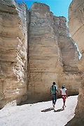 Israel, a couple walking through a canyon in the judea desert