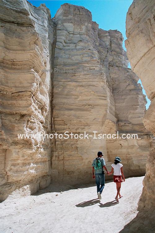 Israel, a couple walking through a canyon in the judea desert