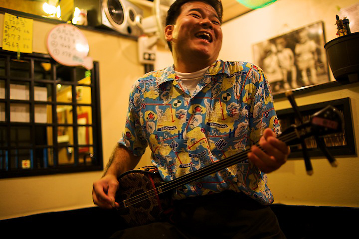 Bridging two worlds.  This restaruanteur in Naha, Okinwa, knew that the Minnesota Vikings just beat the Green Bay Packers.  After dinner, he entertained guests by playing sanshin, the traditional, three-stringed guitar.