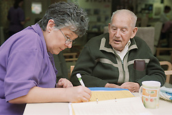 Elderly man talking to female staff nurse while she makes assessment on progress,