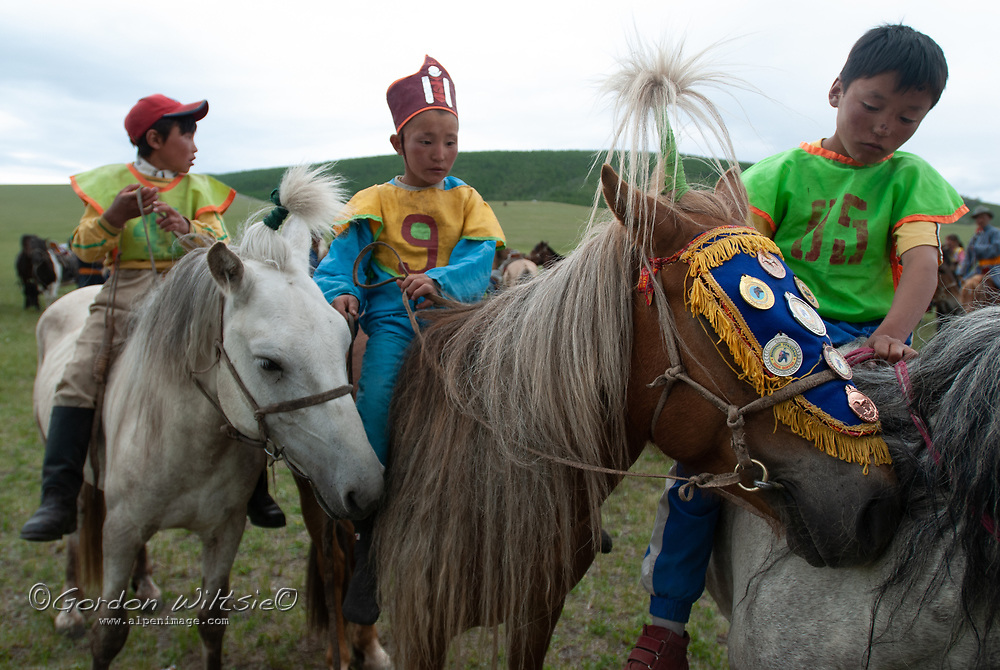 MONGOLIA. Young, costumed  riders - some  bareback- after winning a 20km race at a traditional naadam festival on a remote pass in Arbulag Sum, near Muren in Hovsgol Aimag, Mongolia. The horse's medals are from earlier races and are a great source of family honor.