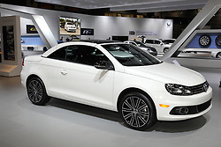 """08  February 2013: 2013 Volkswagon Eos Sport 2.0L turbocharged automobile. Chicago Auto Show, Chicago Automobile Trade Association (CATA), McCormick Place, Chicago Illinois<br /> <br /> 2013 VOLKSWAGEN EOS: What makes the VW Eos stand out in the North America retractable roof market is that it's the only hardtop convertible with a built-in power sunroof. With its unique four-mode retractable hardtop, the 2013 Volkswagen Eos provides year-round driving enjoyment - rain or shine. In addition to the launch line-up of Komfort, Lux and Executive models, a new, more sport-focused models Sport trim has been added for 2013. All trim levels are equipped with the advanced turbocharged/intercooled 2.0-liter four-cylinder engine that cranks-out 200 horsepower and 207 lb. ft. of torque to the front wheels via a fast-shifting six-speed dual-clutch automatic transmission. First drop of rain, and the top is up in 25 seconds. For entertainment, all Eos models come standard with an eight-speaker touchscreen sound system complete with crystal-clear HD Radio technology, an in-dash six-CD changer, and a Media Device Interface (MDI) with iPod cable to seamlessly navigate playlists, albums and more, plus Bluetooth connectivity. The new top-of-the-line Executive package adds a sport-tuned suspension, 18-inch Kansas alloy wheels, RNS 510 navigation system, and a premium sound system from the Danish hi-fi specialist Dynaudio that delivers a true 600 watts, HD radio and 10-speakers. With the Eos's top raised, the trunk offers a generous 10.5 cubic feet of storage space. With the roof fully-retracted, there is still a usable 6.6 cubic feet. For longer items, a lockable pass-through is integrated into the Eos's rear seats. As VW touts it, the Eos is """"a convertible for all seasons."""""""