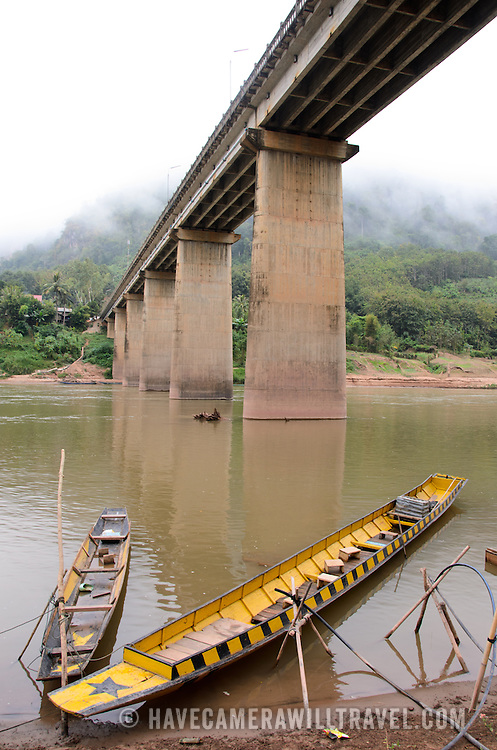 Long, thin wooden canoes tied to the shore of the Nam Ou under the bridge in Nong Khiaw, in northern Laos.