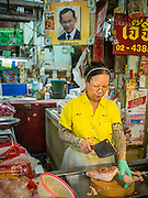 09 DECEMBER 2014 - THONBURI, BANGKOK, THAILAND: A poultry vendor cuts up a chicken in her market stall in Thonburi. She's wearing yellow in honor of Bhumibol Adulyadej, the King of Thailand, whose portrait hangs behind her. Yellow is considered the color of the Monarchy because in Thai culture and astrology yellow is associated with Monday and the King was born on a Monday.    PHOTO BY JACK KURTZ