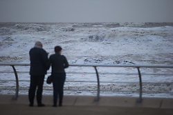 "© Licensed to London News Pictures . 10/12/2014 . Blackpool , UK . Two people look out at the choppy sea . An explosive cyclogenesis - a fast developing storm in which air pressure falls rapidly - known as a "" weather bomb "" - hits the North of England , bringing storms to the region . Photo credit : Joel Goodman/LNP"