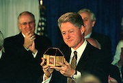 US President Bill Clinton is gifted a Tzedakah box or charity box made in 1435 in Eastern Europe before addressing the National Jewish Democratic Council November 2, 1995 in Washington, DC.