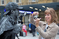 © licensed to London News Pictures. London, UK 26/09/2013. A woman taking picture of a street entertainer who taking part at the opening of King's Cross Square. The square becomes London's newest public space. Photo credit: Tolga Akmen/LNP