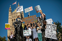 © Licensed to London News Pictures. 20/09/2019. London, UK. Schoolchildren carrying placards calling for action on climate change stand on a statue outside Parliament as tens of thousands join the Global Climate Strike in London. Protests about the climate crisis are being led by young people in cities around the world, with millions expected to attend. Photo credit: Rob Pinney/LNP