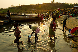 Villagers wait for fishermen to bring back their catch to sell to the local market in the village of Katumbi on Lake Tanganyika in Tanzania August 27, 2011. (Photo by Ami vitale)