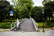 In Rotterdam fietst een verpleegkundige over een brug in het museumpark.<br /> <br /> In Rotterdam a nurse cycles on a bridge in the museum park.