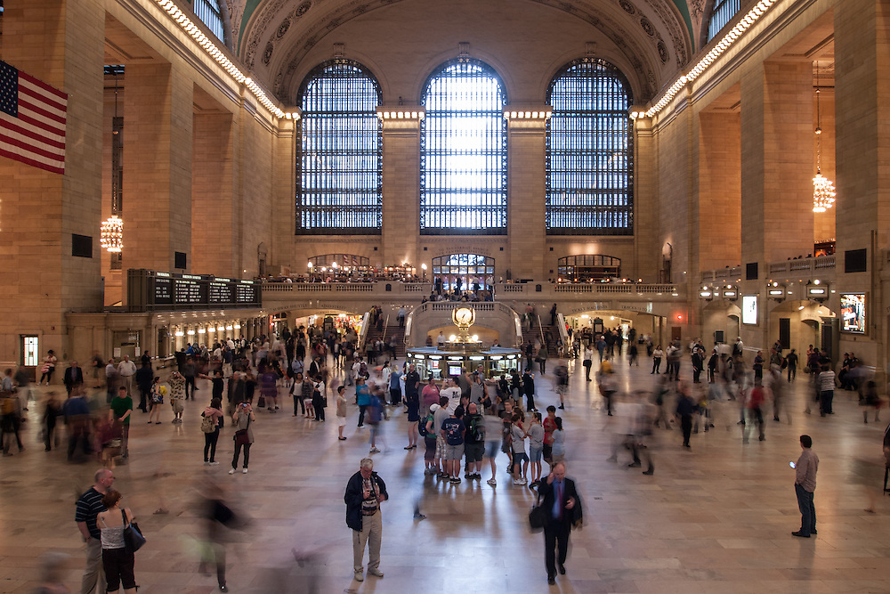 Commuters rush through the concourse of New York's Grand Central Terminal on a busy afternoon. The station was designed by the firm of Reed & Stem, with the facade by Warren & Wetmore, and was opened in 1913.