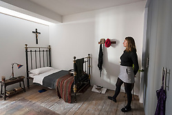 "© Licensed to London News Pictures. 13/11/2018. LONDON, UK. A staff member stands in Ruth Ellis' prison cell.  Preview of ""Glad I Did It"", a new work by Irish artist Christina Reihill at Bermondsey Project Space.  The interactive artwork looks at the life and death of Ruth Ellis, the last woman to be hanged in Britain, after she shot her lover, racing driver, David Blakely in 1955.  On display are the artist's interpretation of Ruth Ellis' prison cell, including furniture and props, the hanging room together with a video display of the artist in conversation.   The show runs 14 November to 1 December 2018.  Photo credit: Stephen Chung/LNP"