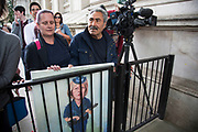 Political artist Kaya Mar with his latest painting behind bars on the day that the new Conservative Party leader Theresa May MP became Prime Minister of the UK, as protesters and public gathered outside Downing Street on 13th July 2016 in London, United Kingdom. This painting portrays Theresa May as a thuggish police woman holding a truncheon with a nail through it. Political satire on her hardline dealings with the police force.