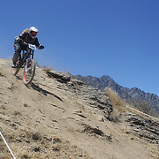 Amy Freedman from Queenstown in action during the New Zealand South Island Downhill Cup Mountain Bike series held on The Remarkables face with a stunning backdrop of the Wakatipu Basin. 150 riders took part in the two day event. Queenstown, Otago, New Zealand. 9th January 2012. Photo Tim Clayton