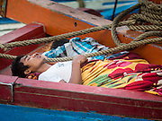 27 OCTOBER 2015 - YANGON, MYANMAR: Crewman on a trawler sleep in the market at Aungmingalar Jetty in Yangon. The market is home to one of the largest fish markets in Yangon and a meat and produce market.    PHOTO BY JACK KURTZ