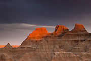 The golden light of sunset shines through a narrow crack in an otherwise dreary fall sky to light up the peaks of several large formations in the Badlands of South Dakota.