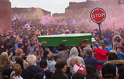 Glasgow, Scotland, UK. 15 May 2021. Thousands of supporters and fans of Rangers football club descend on Ibrox Park in Glasgow to celebrate winning the Scottish Premiership championship for the 55nd time and the first time for 10 years. Smoke bombs and fireworks are being let off by fans tightly controlled by police away from the stadium entrances ;PIC Rangers fans carry green coffin signifying end of Celtic's title reign. Iain Masterton/Alamy Live News