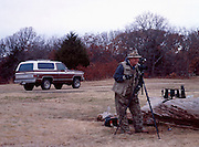 James Pratt taking pictures at Arcadia Lake in Edmond with brown Chevy Blazer in background
