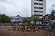 Housing estate tower blocks behind a demolished construction site at Holloway Circus in Birmingham city centre, which is virtually deserted under Coronavirus lockdown on a wet rainy afternoon on 28th April 2020 in Birmingham, England, United Kingdom. Britains second city has been in a state of redevelopment for some years now, but with many outdated architectural remnants still remaining, on a grey day, the urban landscape appears as if frozen in time. Coronavirus or Covid-19 is a new respiratory illness that has not previously been seen in humans. While much or Europe has been placed into lockdown, the UK government has put in place more stringent rules as part of their long term strategy, and in particular social distancing.