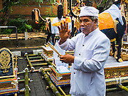 16 JULY 2016 - UBUD, BALI, INDONESIA:  A Hindu priest waks among the sarcophagus and preays before the mass cremation in Ubud Saturday. Local people in Ubud exhumed the remains of family members and burned their remains in a mass cremation ceremony Wednesday. Almost 100 people were cremated and laid to rest in the largest mass cremation in Bali in years this week. Most of the people on Bali are Hindus. Traditional cremations in Bali are very expensive, so communities usually hold one mass cremation approximately every five years. The cremation in Ubud concluded Saturday, with a large community ceremony.     PHOTO BY JACK KURTZ