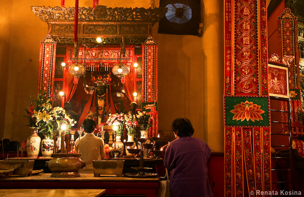 Women lighting candles inside a temple in the center of Hong Kong