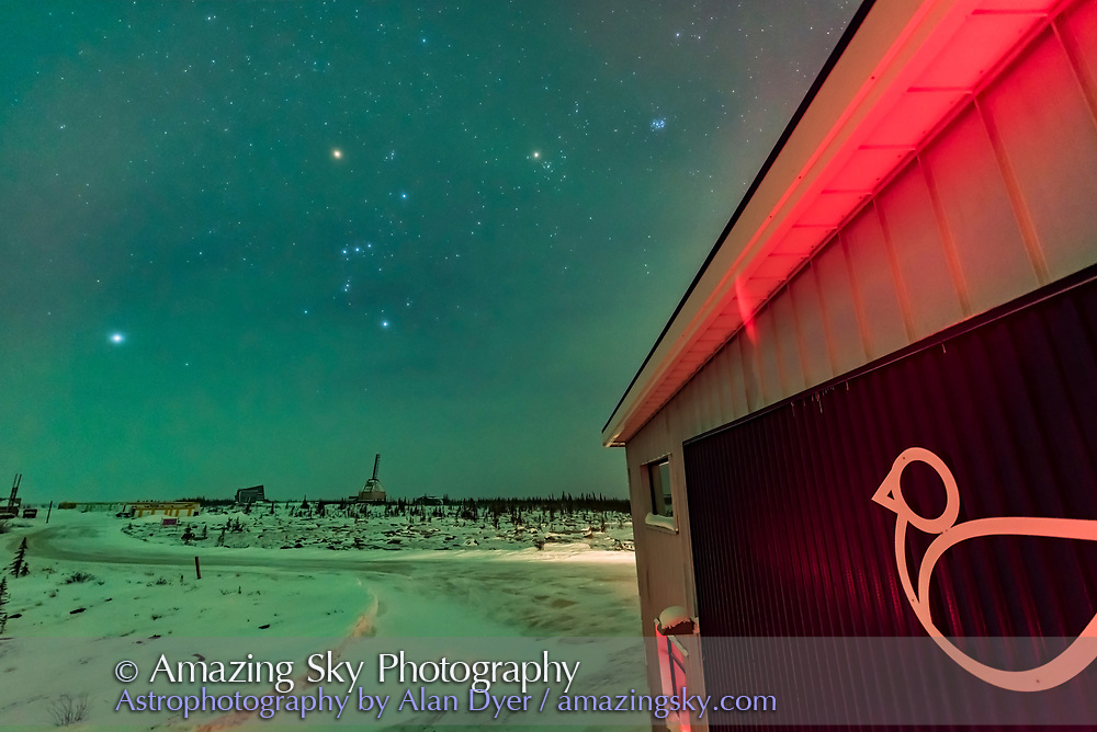 """Orion and the winter stars, with Taurus and Canis Major, with the Churchill Northern Studies Centre building and """"birdfish"""" logo in the foreground. Orion's belt points up the Taurus, with Aldebaran and the Pleiades, and also points down to Canis Major with the bright star Sirius. <br /> <br /> This is a single 8-second exposure with the 14mm Sigma Art lens at f/1.8 and Nikon D750 at ISO 3200. Taken Feb 8, 2018 on a partly cloudy  night with aurora to the north lighting the sky and ground green. The clouds added the natural star glows and accentuated their colours. <br /> <br /> The launch towers from the abandoned Churchill Rocket Range are in the distance."""