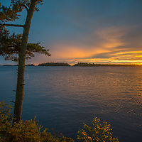A sunset glows behind islands in Lake of the Woods, Ontario, Canada.