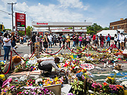 """12 JUNE 2020 - MINNEAPOLIS, MINNESOTA: A women prays at the impromptu memorial for George Floyd at the corner of 38th Street and Chicago Ave. in Minneapolis. The intersection is informally known as """"George Floyd Square"""" and is considered a """"police free zone."""" There are memorials to honor Black people killed by police and people providing free food at the intersection. Floyd, an unarmed Black man, was killed by Minneapolis police on May 25 when an officer kneeled on his neck for 8 minutes and 46 seconds. Floyd's death sparked weeks of ongoing protests and uprisings against police violence around the world.          PHOTO BY JACK KURTZ"""
