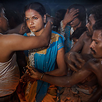 """An Aravani is """"married"""" to Lord Krishna's in a temple ceremony in Koovagam...India's transexual community has a recorded history of more than four thousand years. Many consider the The Third Sex, also known as Aravanis, to posses special powers allowing them to determine the fate of others. As such, they are not only revered but despised and feared too. Resigned to the fringes of society, segregated and excluded from most occupations, many Aravanis are forced to turn to begging and sex work in order to earn a living. ..The annual transgender festival in the village of Koovagam, near Vilappuram, offers an escape from this often desolate existence. For some, the week-long partying and frenetic sex trade that culminates in the Koovagam festival is about fulfilling lustful desires. For others, the gathering provides a chance for transgenders to bond, share experiences, join the wider homosexual gay-community and coordinate their campaign for recognition and tackle the challenge of HIV/AIDS. ..It is the Indian state of Tamil Nadu that the eighty-thousand-strong Aravani community has made advances in their fight for rights. In 2009, the Tamil Nadu state government began providing sex-change surgery free of cost. The state has also offers special third-gender ration cards, passports and reserved seats in colleges. And 2008 the launch of Ippudikku Rose, a Tamil talk-show fronted by India's first transgender TV-host and the release of a mainstream Tamil film staring an Aravani in the lead-role. ..These advances clearly signal a victory for south India's transgenders, but they have also exposed deep divisions within the community. There is a very real gulf that separates the majority poor from their potentially influential but often reticent, upper-class sisters. ..Photo: Tom Pietrasik.Vilappuram District, Tamil Nadu. India.May 2009"""