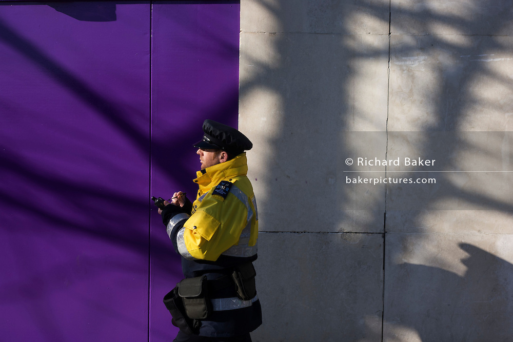 A Civil Parking Enforcement Officer walks past a purple construction hoarding screen on a London street.