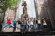 Studenten springen op het Domplein in Utrecht voor een opdracht tijdens de introductieweek. Vandaag zijn in Utrecht de introductiedagen, onder de noemer UIT, van start gegaan. Eerstejaars studenten maken onder begeleiding van ouderejaars kennis met elkaar en de stad waar ze gaan studeren.<br /> <br /> Students are jumping for a photo at the Domplein in Utrecht during their introduction week of the Utrecht University.
