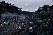 Full moon and debris of fishing equipments at a fishing port in Minamisanriku town.