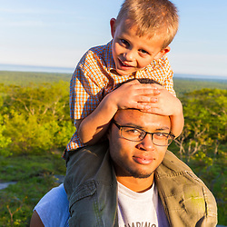 A teenage boy carries his young cousin near the summit of Mount Agamenticus in York, Maine.