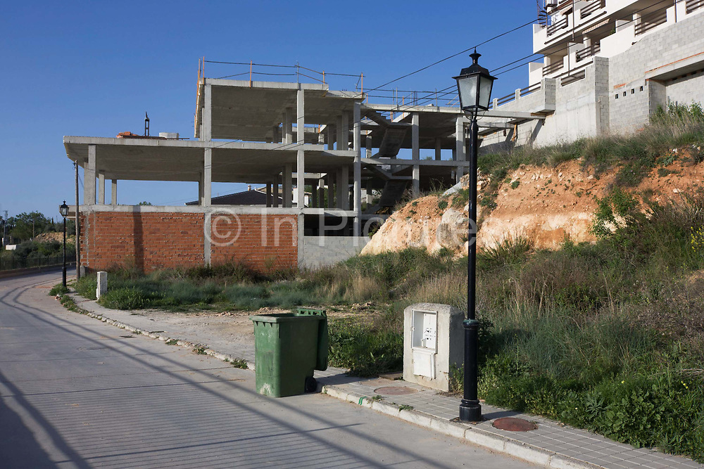 An unfinished and abandoned construction project in the town of Gogollos Vega, near Granada, Andalucia. All over Spain are building projects like this, left empty and unused, a sig of bad financial investment and land management where empty lots and landscapes have swallowed nature to be replaced by abandoned pavements, roads and superstructures. Here, we see a lone lamppost on the street's kerb, a green waste bin and an overgrown lot where weeds are thriving in this wilderness. In the background is a generic two-storey building left unfinished. As of 2010, it has a population of 2,068 inhabitants.