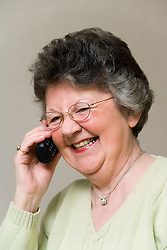Woman chatting on the telephone; smiling,