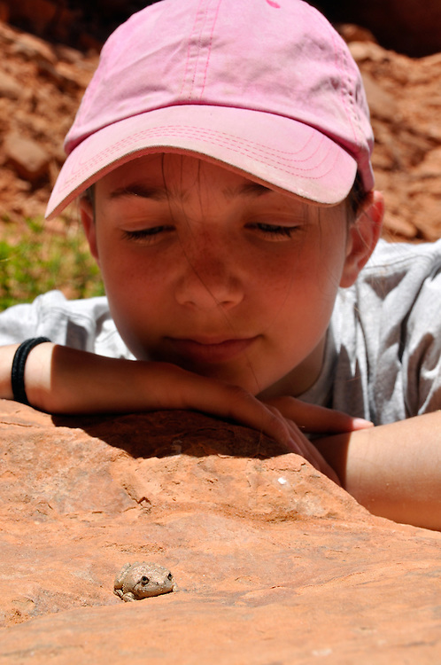 Girl taking a close look at a toad in Utah's Escalante Canyon.